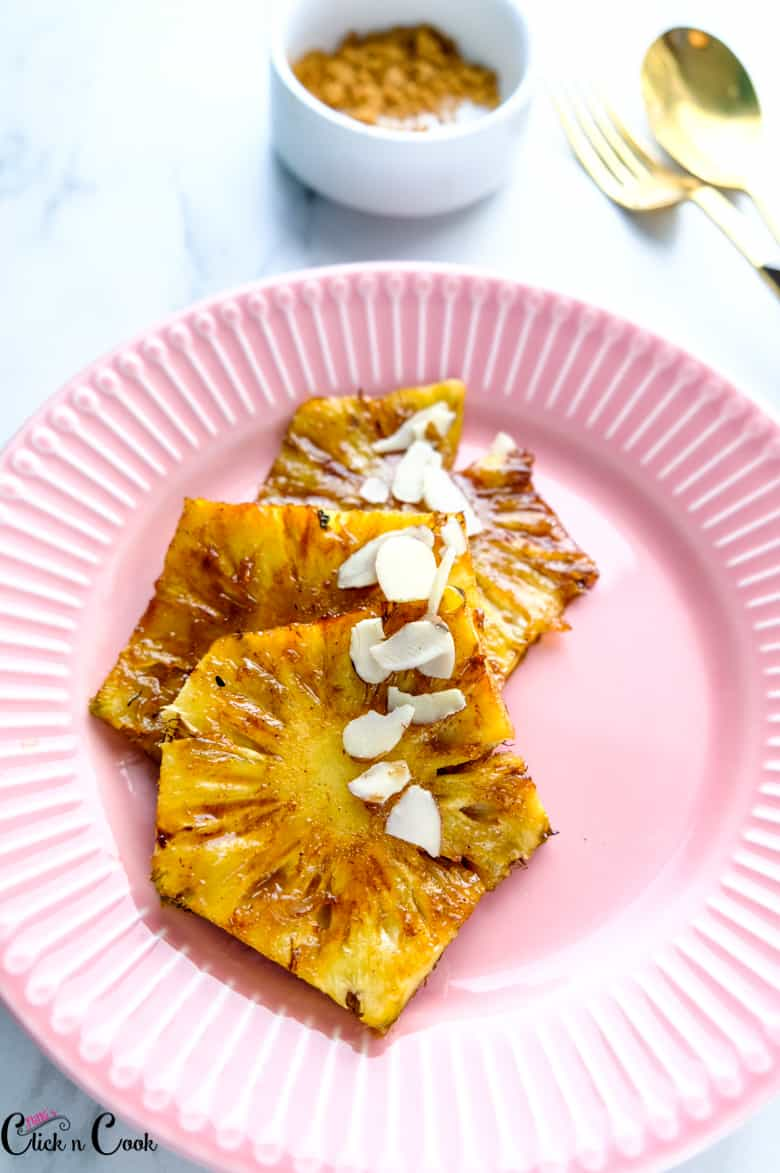 grilled pineapple served in pink plate