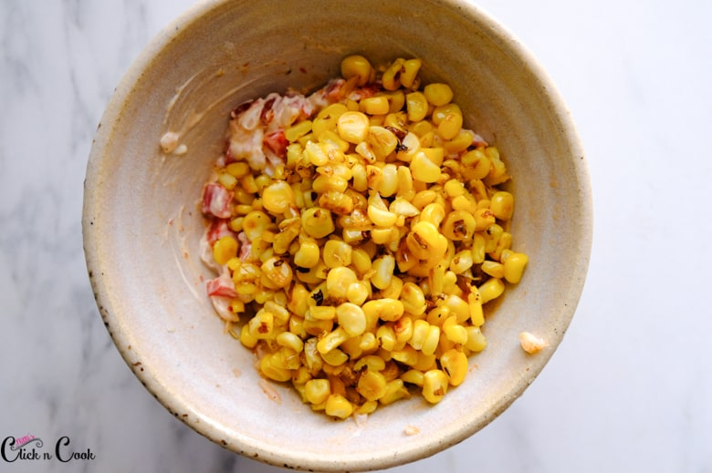 grilled corns with the dressing in mixing bowl