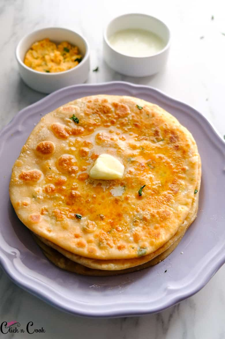 paneer paratha served in grey plate with butter on top