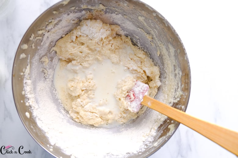 milk and batter is being mixed using steel bowl