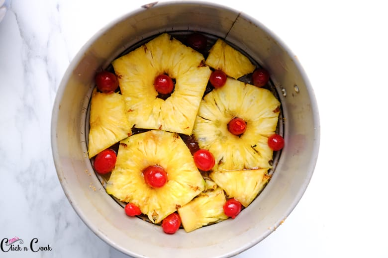 pineapple slices and cherries are arranged in cake pan to make pineapple cake