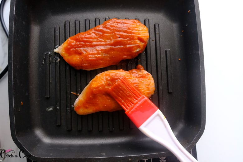 barbecue sauce is being brushed over the chicken breast and grilled on the grilled pan