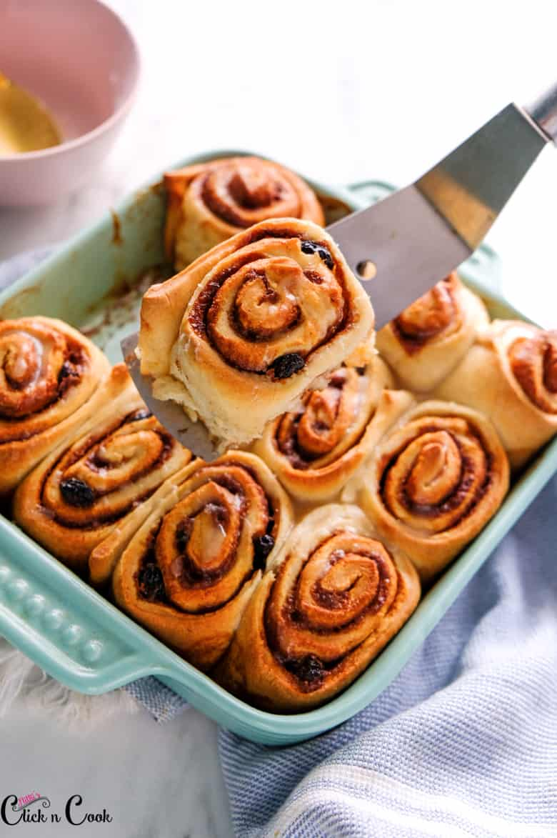 cinnamon rolls in baking tray is being taken using spatula