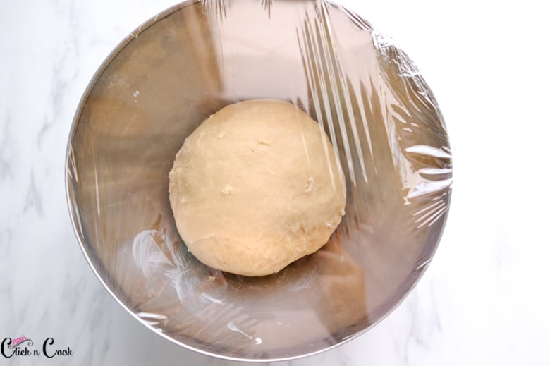 rolled dough in mixing bowl with wrapped in cling wrap