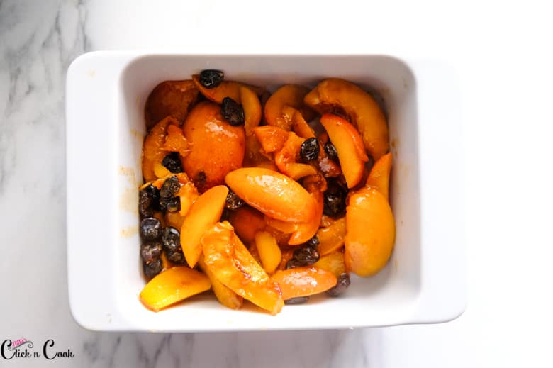 sliced peaches and raisin in the white baking dish