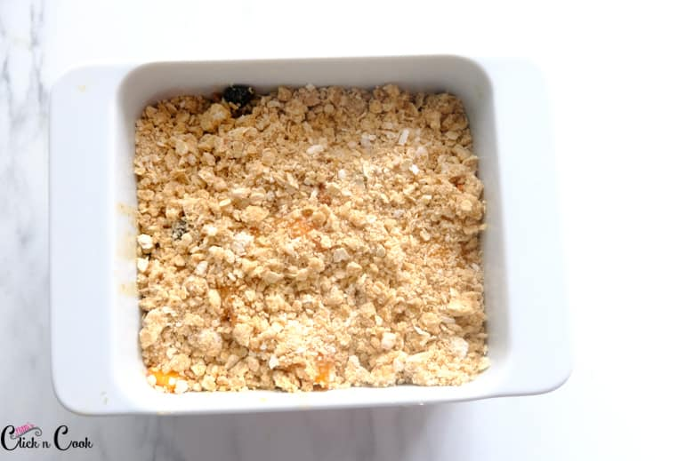oatmeal crumbs are sprinkled over the peach filling in the white baking dish
