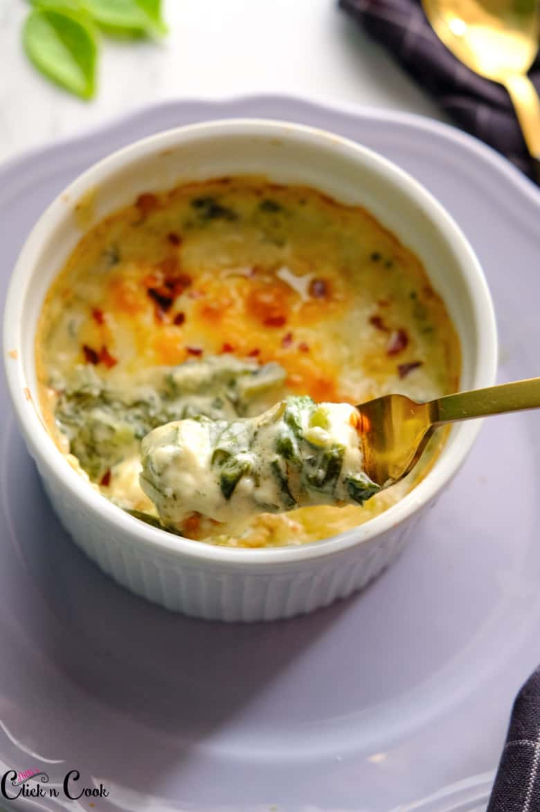 A spoon of spinach dip is taken from the white bowl