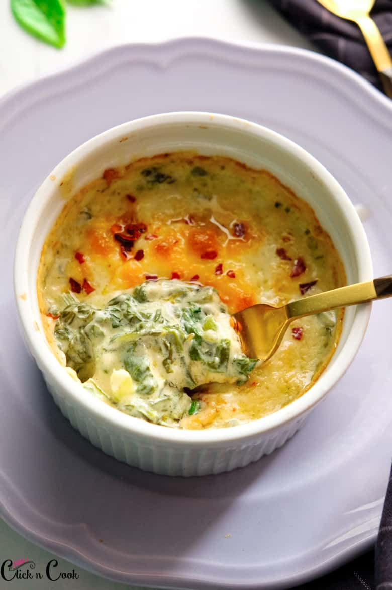spinach dip recipe is in white ceramic bowl on the grey plate