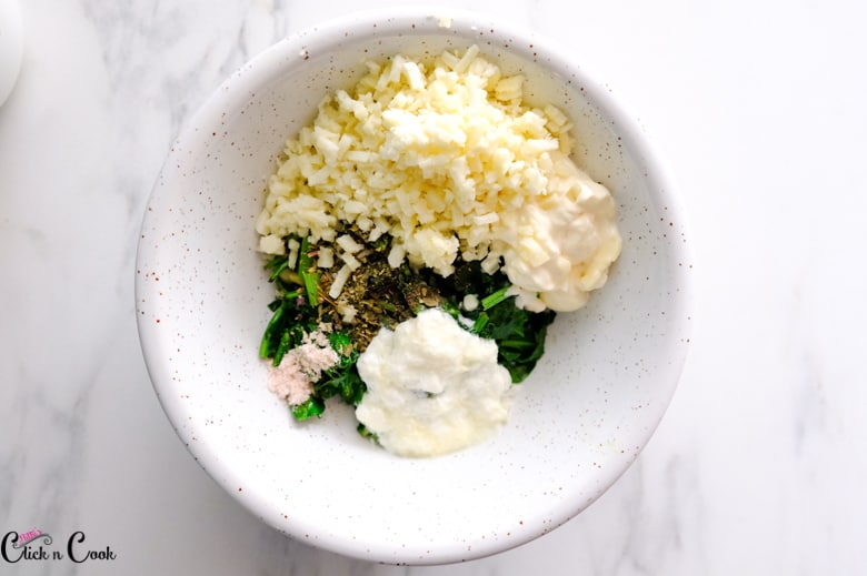 wilted spinach, cheese, cream and yogurt is in white bowl