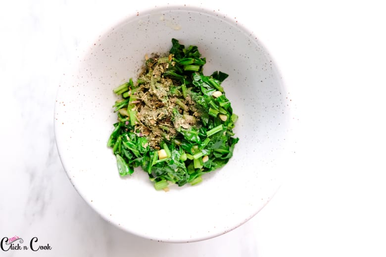 wilted spinach, pepper powder and herbs are in white bowl