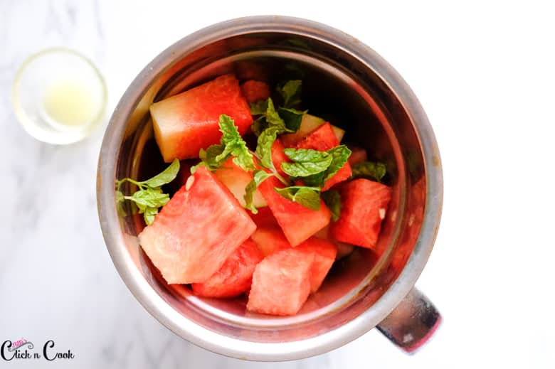 chopped watermelon and mint leaves in blender