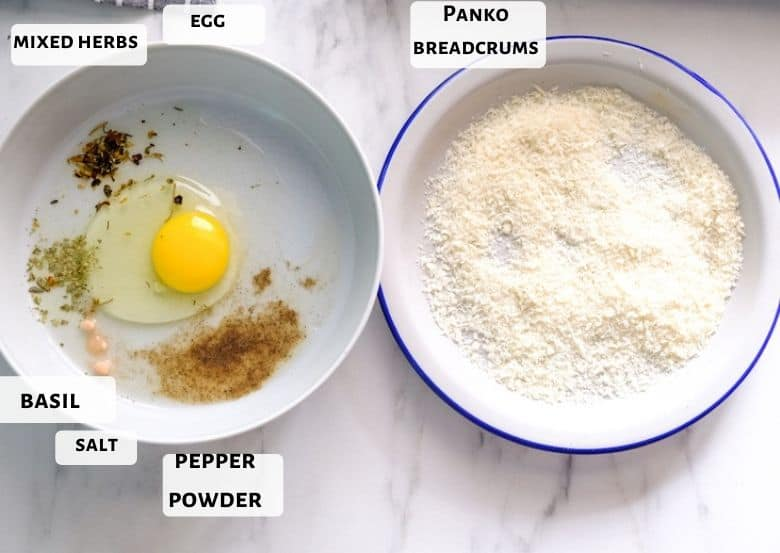 Egg and spices are in bowl and bread crumbs on the plate.