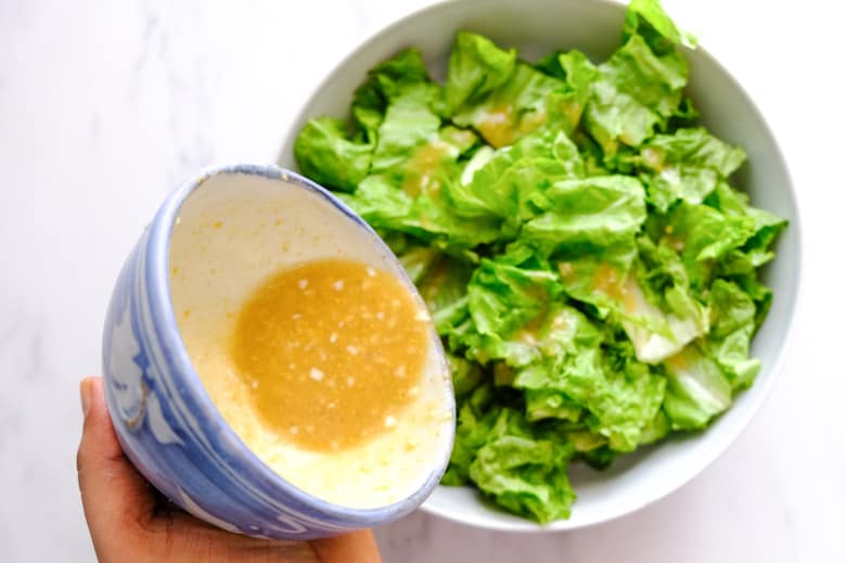 The caesar dressing from the glass bowl is being added to the lettuce in a grey bowl.