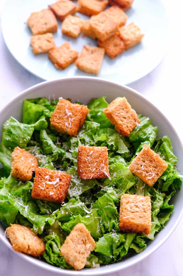 Caesar salad recipe is served on a glass bowl and topped with garlic croutons.