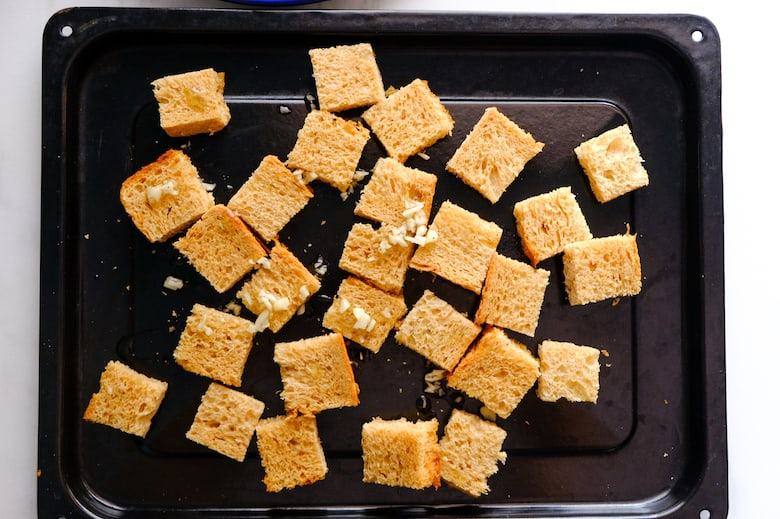 Cubed bread placed on the black baking tray