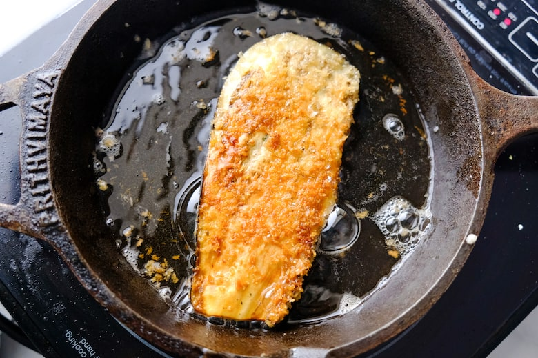 Eggplant is being fried in olive oil in a cast iron pan.