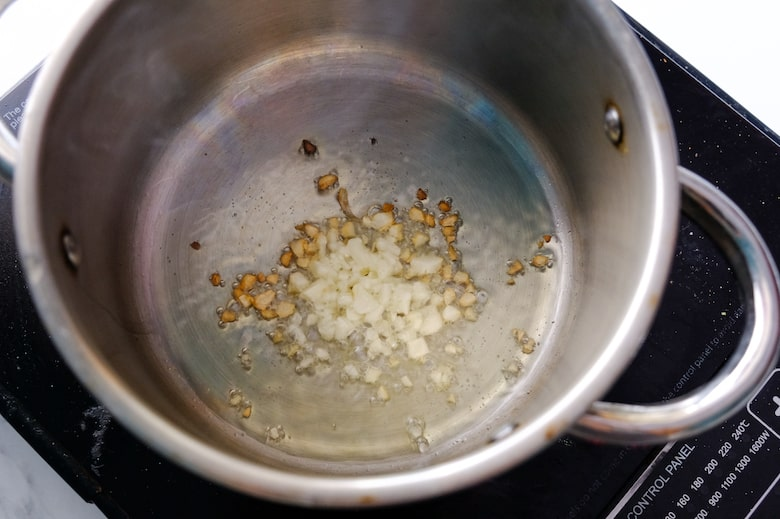 Minced garlic is being cooked in a saucepan