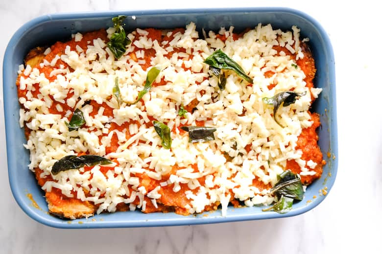 Mozzarella cheese is spread over the eggplant Parmesan in the blue baking tray