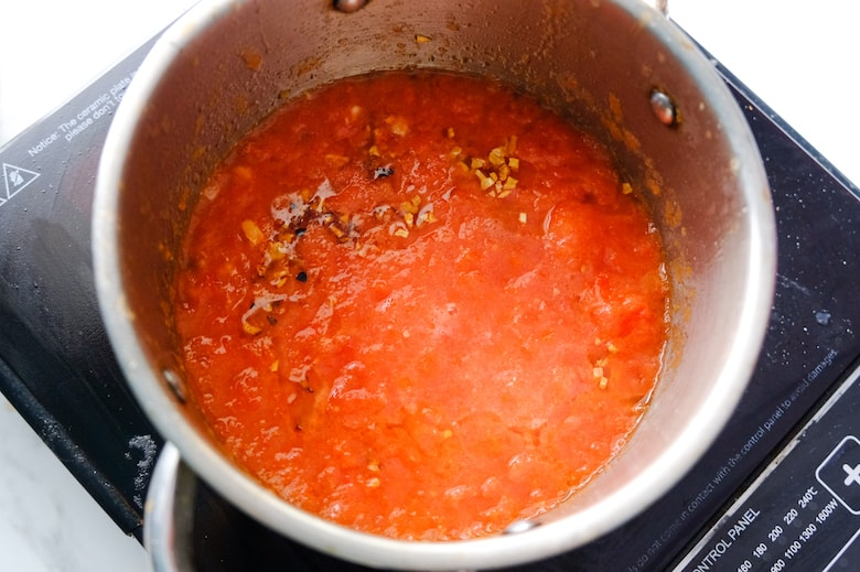 Tomato sauce is being cooked in a saucepan