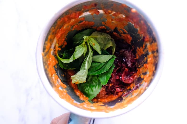 Roasted tomato, beetroot and basil leaves are in blender