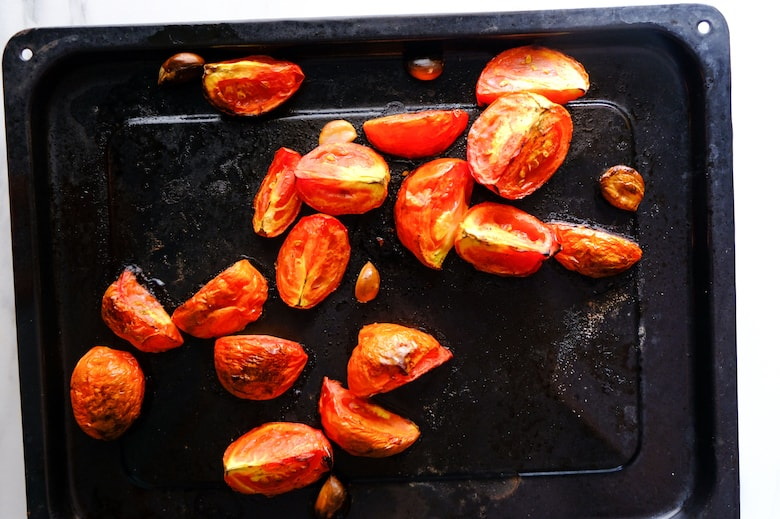 Roasted tomato and garlic are in black baking tray