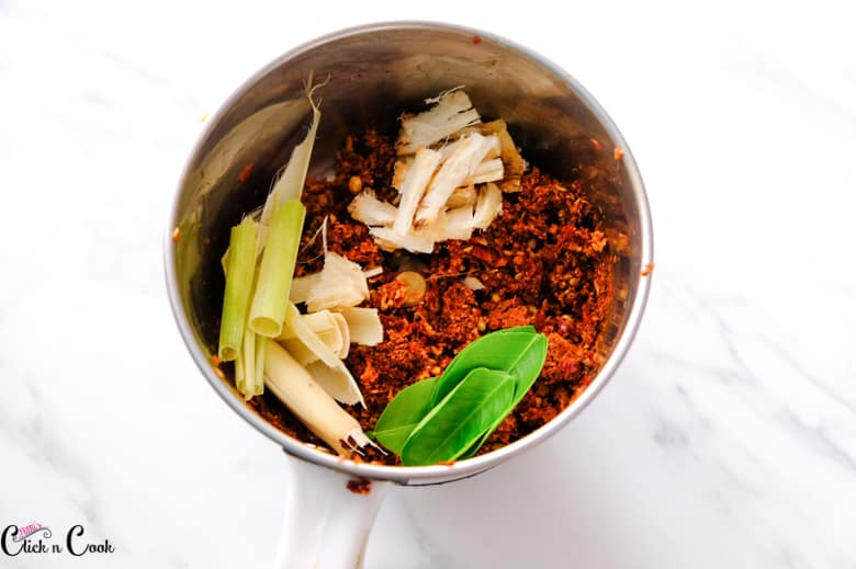 Lemongrass, galangal, and kaffir leaves are in the blender with Thai red curry paste.