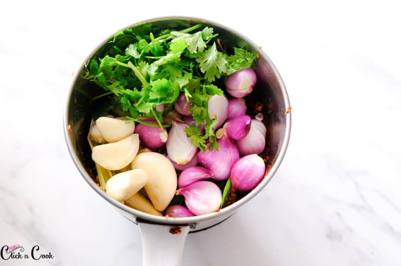 Shallots, garlic, and coriander leaves are in the blender