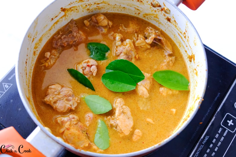 Kaffir leaves are added to Thai red curry chicken in a saucepan.