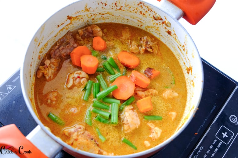 Carrots and beans are being added to Thai red curry that is being cooked in a saucepan.