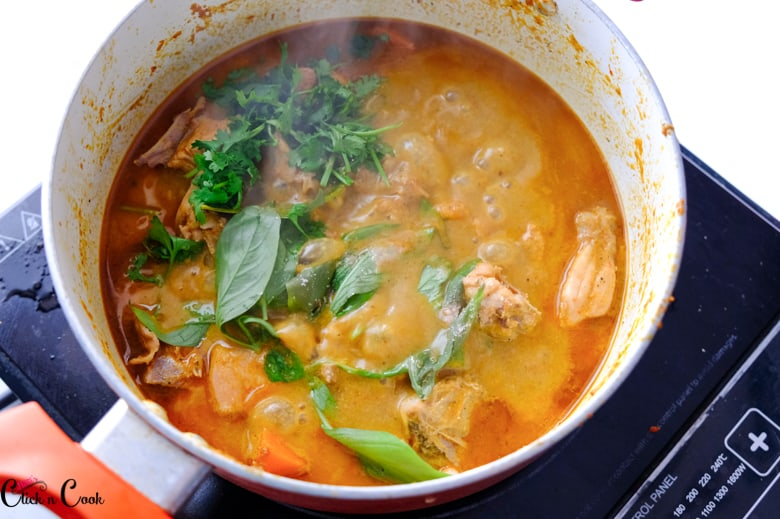 Thai Basil and coriander leaves are being added to Thai red curry in the deep saucepan.