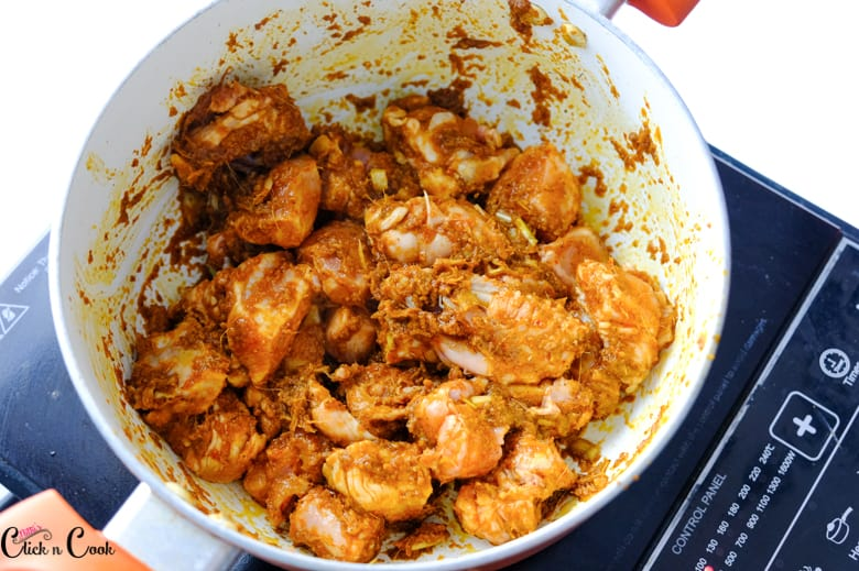 Chicken cooked with spices in the saucepan.