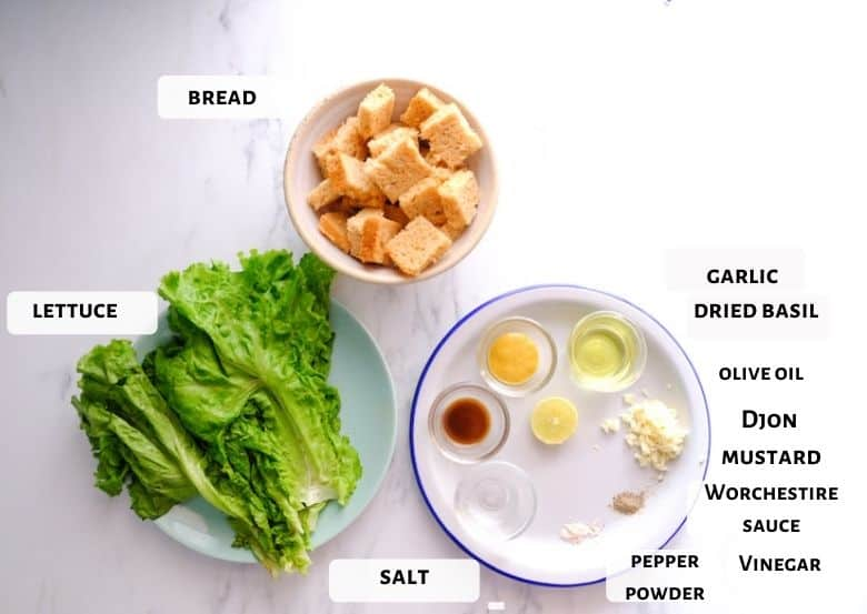 Romaine lettuce, bread, and sauce ingredients are taken in small glass bowls.