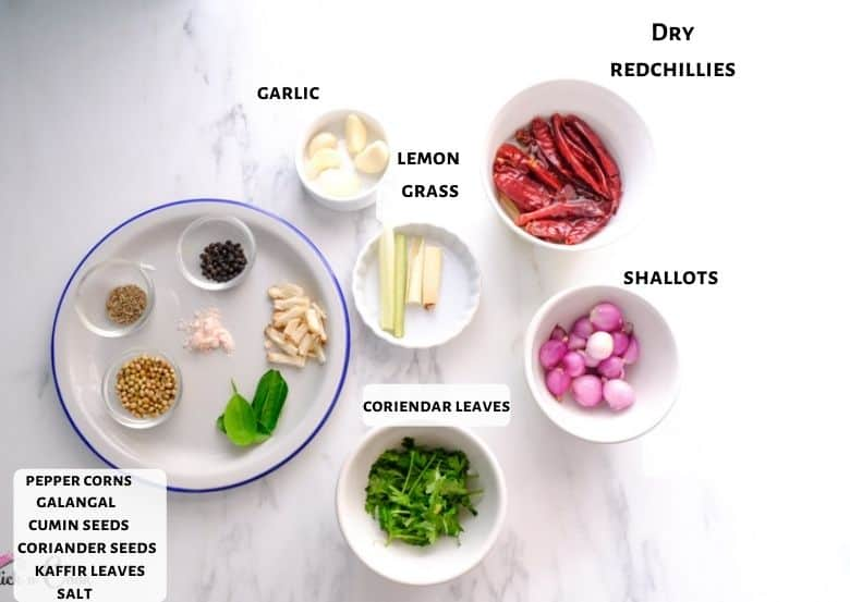 Dry red chilies, shallots, galangal, lemongrass, cumin seeds, coriander seeds are taken in a glass bowl and white plates.