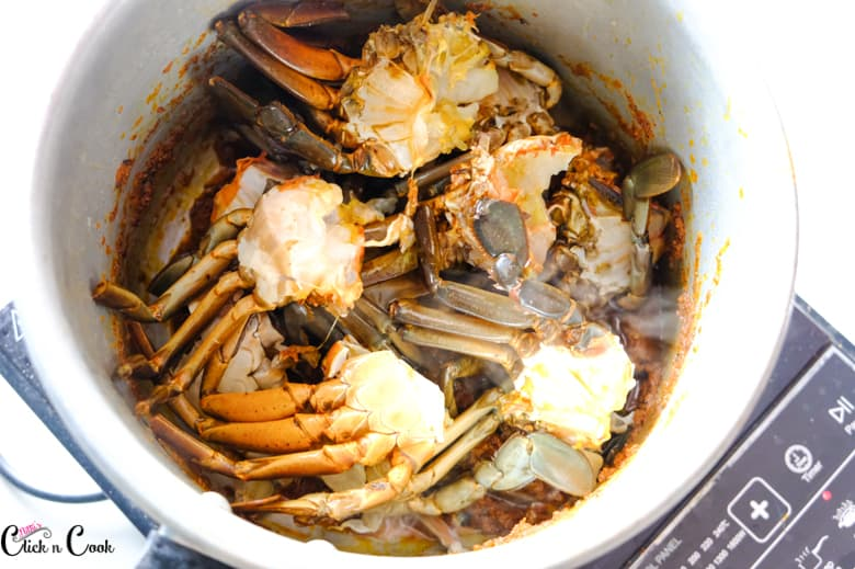 Crab is being added to the saucepan.