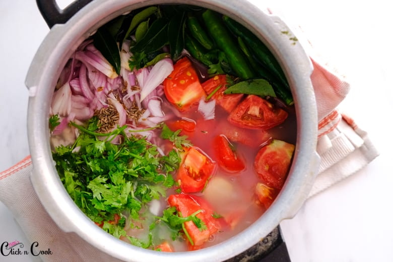 Water is being added to onion, tomato, green chili, coriander leaves that in the pressure cooker.