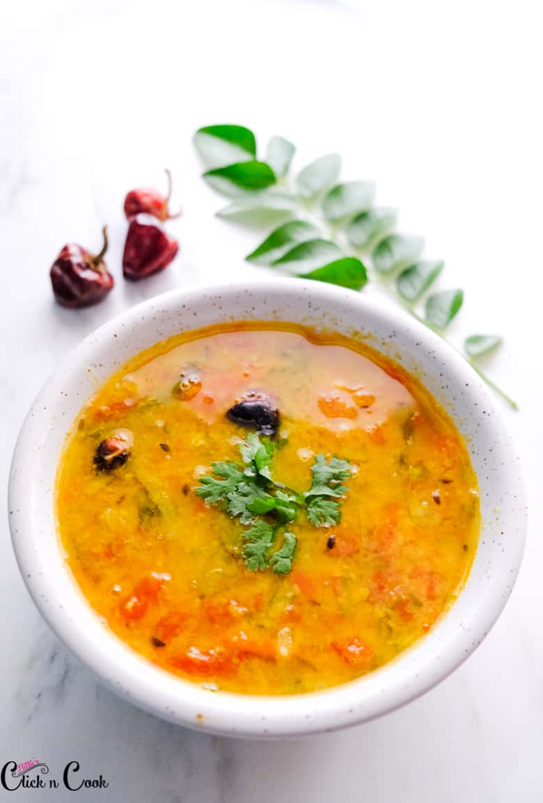 Dry chili sambar served in a white bowl and chopped coriander leaves sprinkled on top.