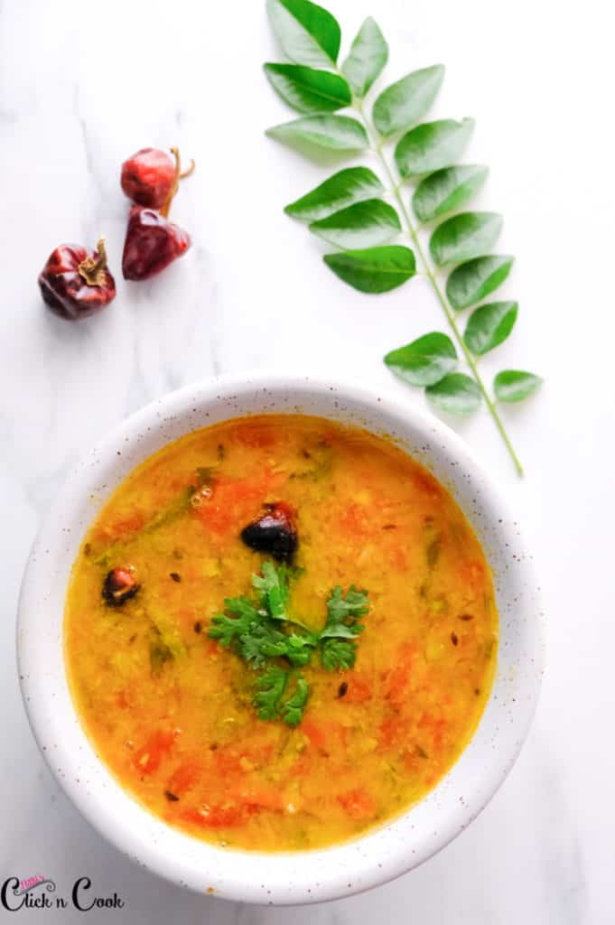 Sambar recipe served in a white bowl, sprinkled with coriander leaves.