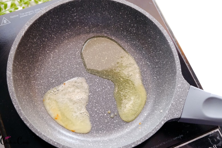 Butter and oil is being heated up in a grey pan