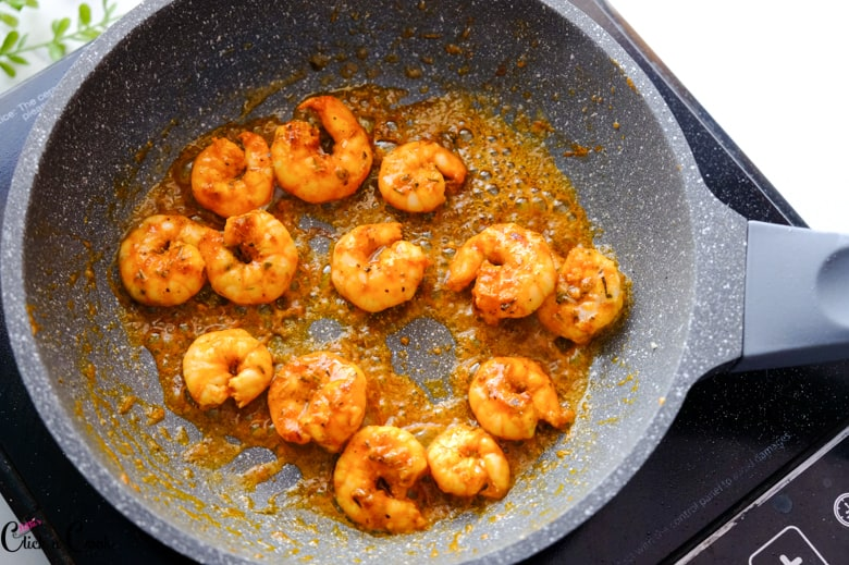 Cajun shrimp are cooked in a grey pan.