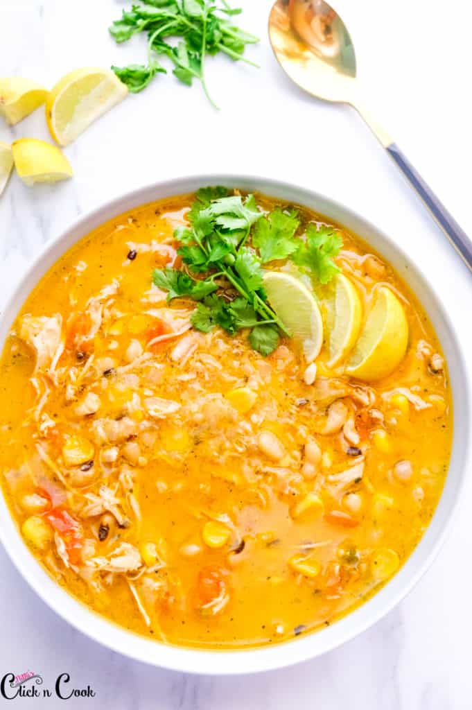 instant pot white chicken chili served in bowl with cilantro and lime wedges