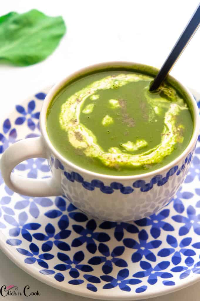palak soup served in a mug placed on the plate with spoon in