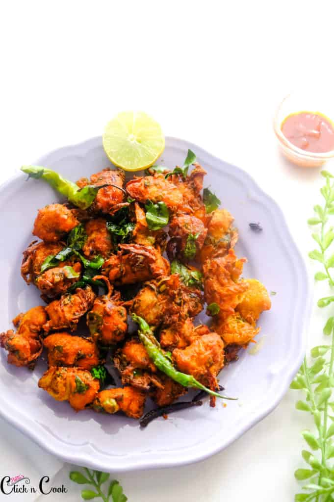 chicken pakora served in grey plate with sliced lemon and green chillies.