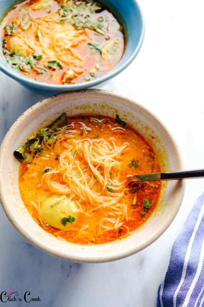 laksa served in a bowl with spoon in.
