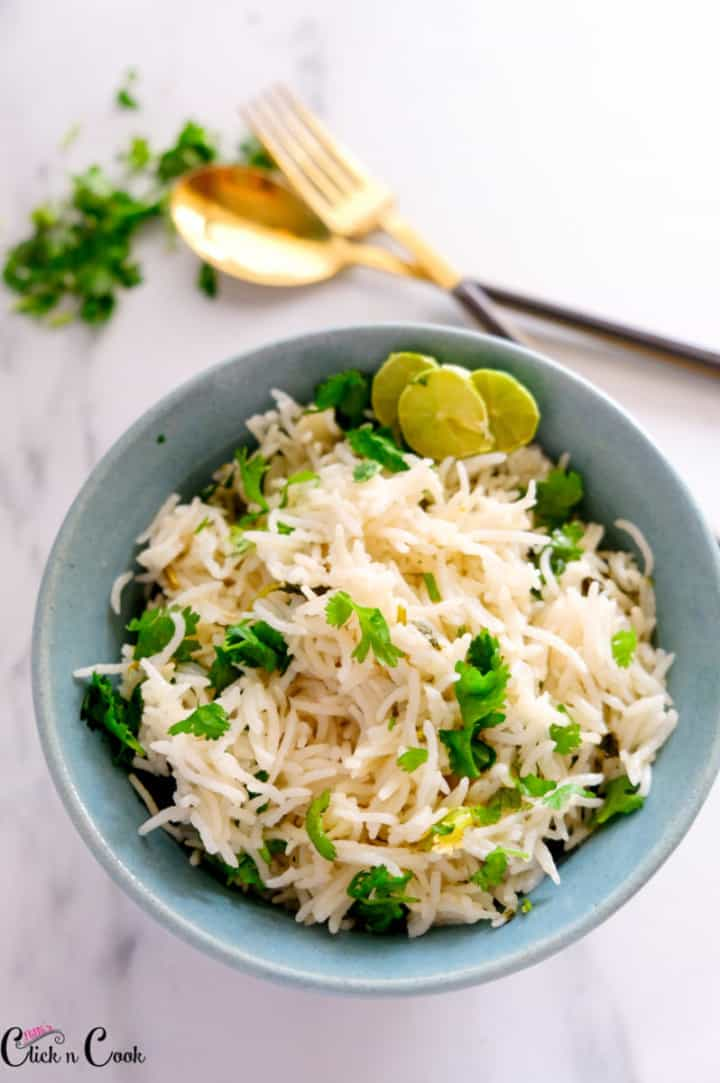 cilantro rice is being served in blue bowl with fork and spoon aside.