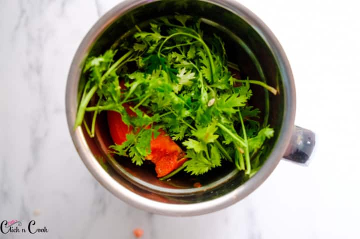 coriander leaves and tomato are in blender