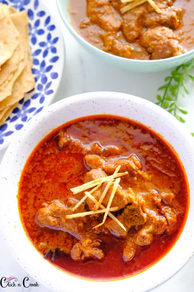 Rogan Josh served in a white bowl with roti aside.