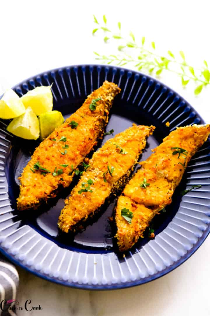air fryer fish on blue plate with sliced lemon aside.