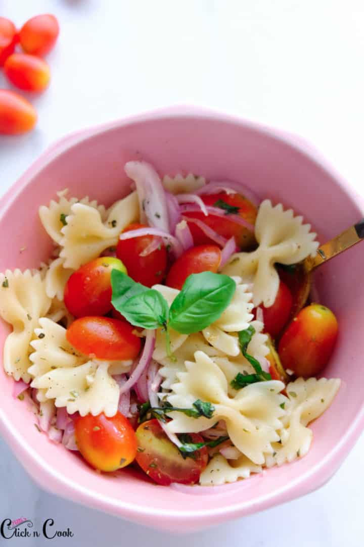cherry tomato pasta salad served in pink bowl